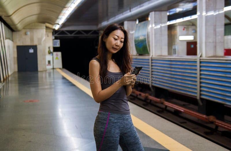 Jeune femme asiatique ? l'aide du t?l?phone portable ? la station de train images stock