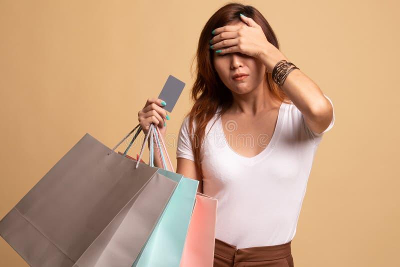 Jeune femme asiatique malheureuse avec les paniers et la carte de cr?dit photographie stock libre de droits