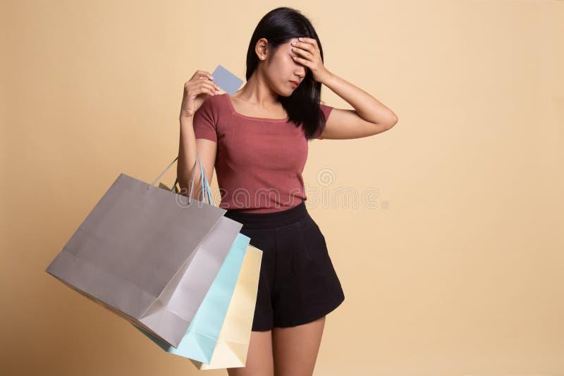 Jeune femme asiatique malheureuse avec les paniers et la carte de cr?dit image libre de droits