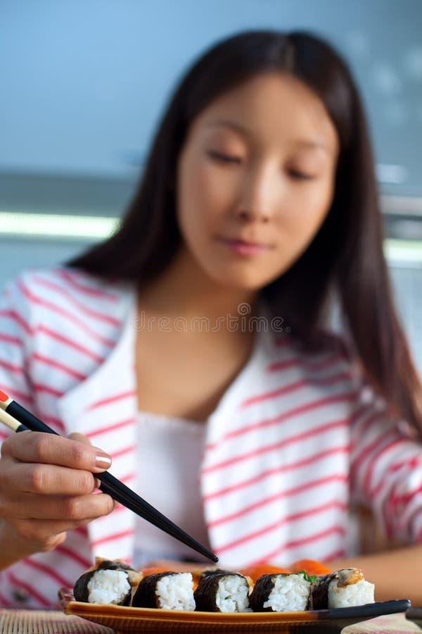 Jeune femme asiatique mangeant des sushi photos libres de droits