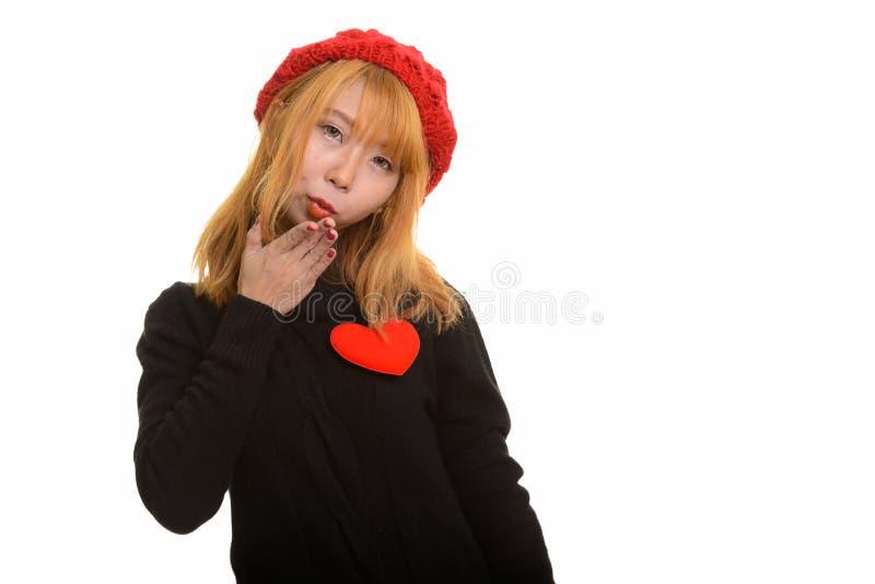 Jeune femme asiatique mignonne avec le coeur rouge sur le coffre et le baiser de soufflement images stock