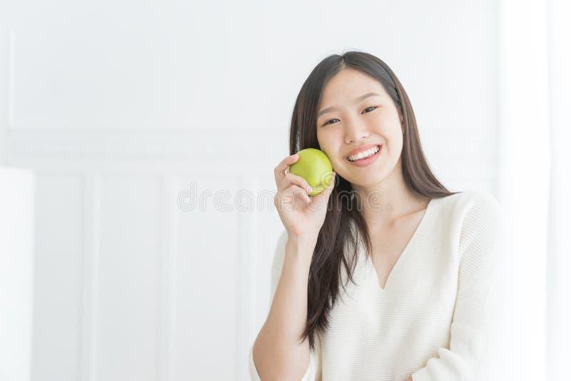 Jeune femme asiatique montrant la pomme verte, à l'intérieur portrait photos stock