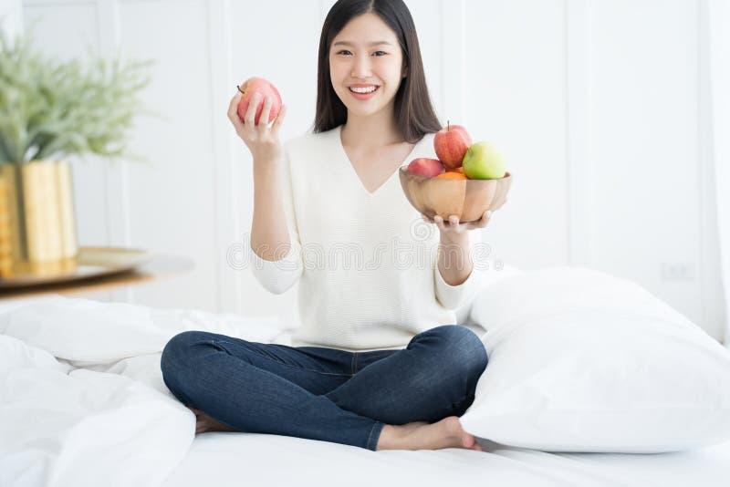 Jeune femme asiatique montrant la pomme verte et la pomme rouge, à l'intérieur portrait images stock