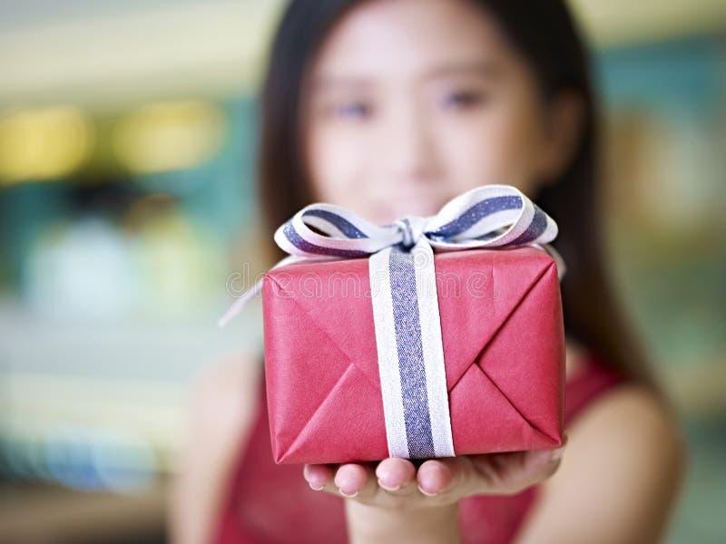 Jeune femme asiatique montrant un cadeau enveloppé photo stock
