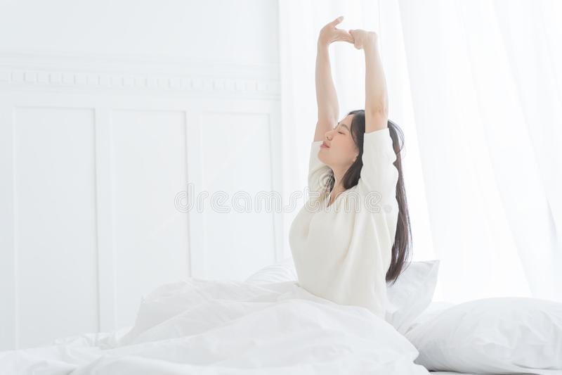 Jeune femme asiatique pendant le matin elle s'étirant dans son lit dans la chambre à coucher image stock