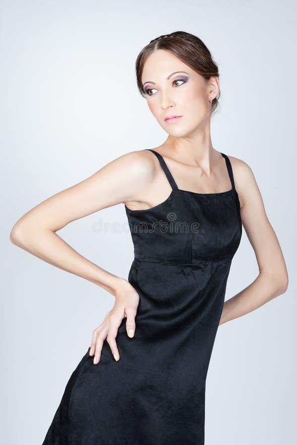 Jeune femme asiatique posant dans le studio dans la robe noire photo stock