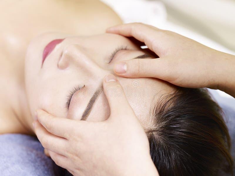 Jeune femme asiatique recevant le massage de visage dans le salon de station thermale photographie stock