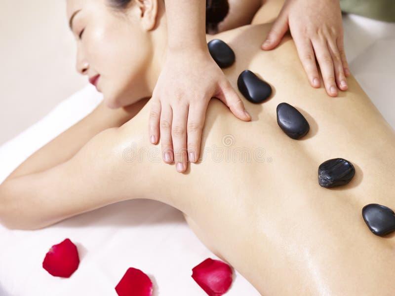 Jeune femme asiatique recevant le massage en pierre chaud dans le salon de station thermale image libre de droits