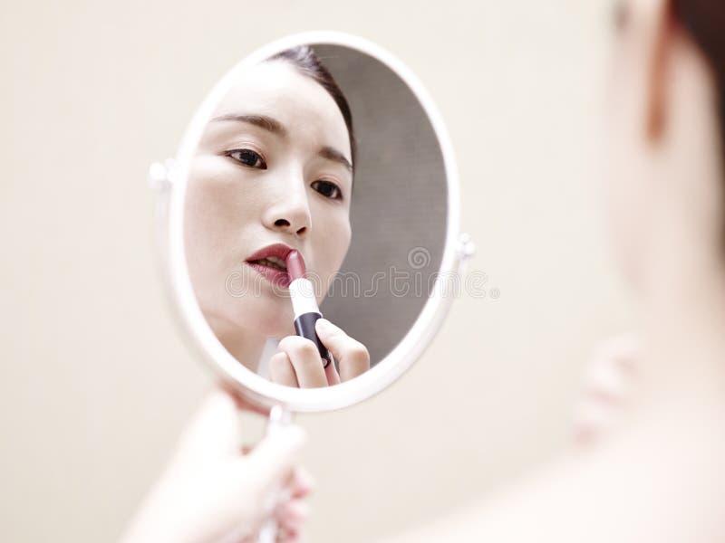 Jeune femme asiatique regardant dans le miroir appliquant le rouge à lèvres photographie stock libre de droits
