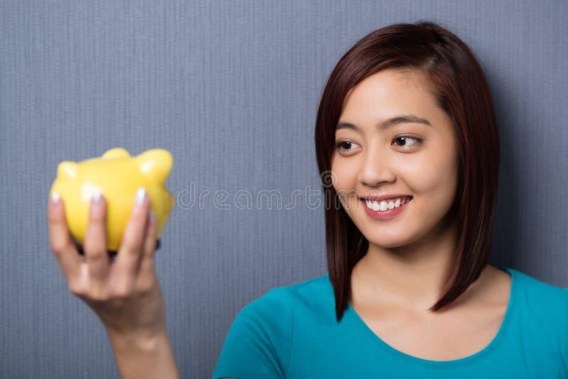 Jeune femme asiatique regardant sa tirelire images stock