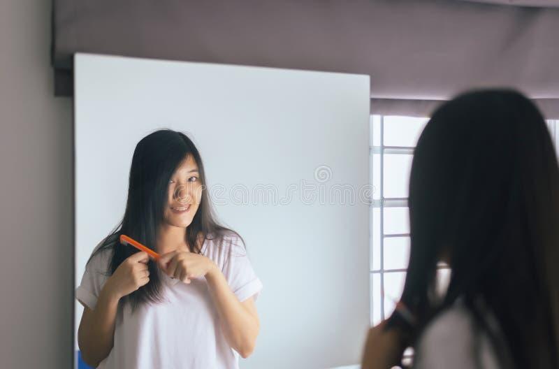 Jeune femme asiatique séchant ses longs cheveux avec l'avant de dessiccateur ou de peigne du miroir photos libres de droits