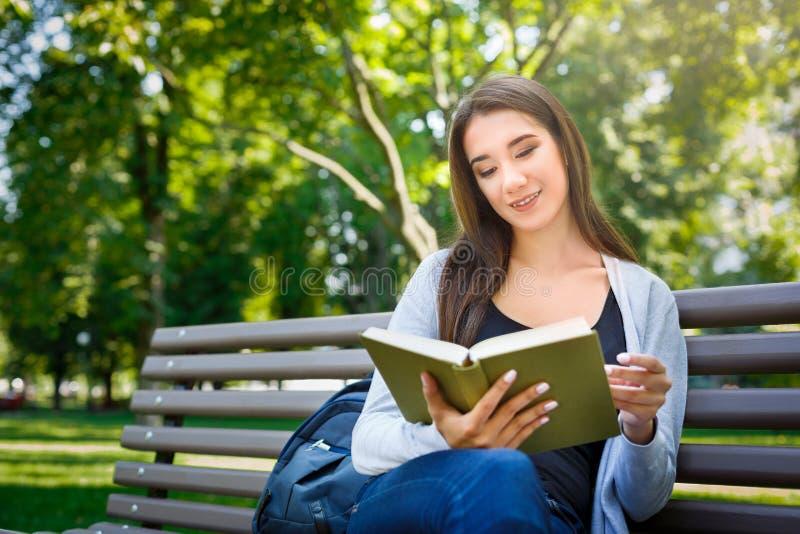 Jeune femme asiatique s'asseyant sur un banc en parc Détendant et lisant un livre photographie stock