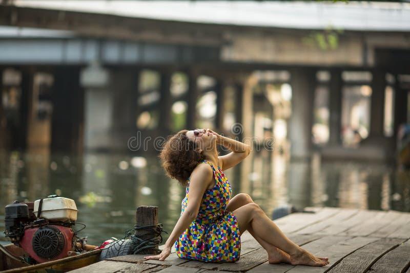 Jeune femme asiatique s'asseyant sur un dock de rivière image libre de droits