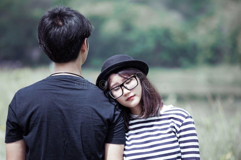 Jeune femme asiatique se reposant sur son épaule du ` s d'ami avec amour image libre de droits