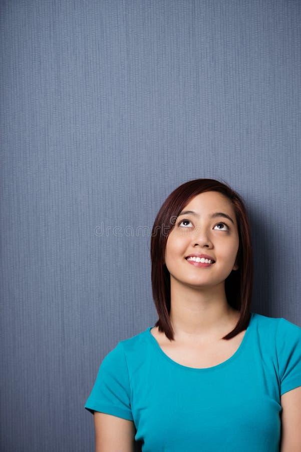 Jeune femme asiatique se tenant rêvassante photographie stock libre de droits