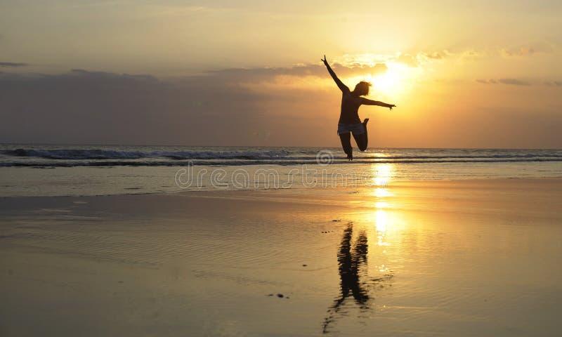 Jeune femme asiatique sexy heureuse dans sauter de bikini excité sur la plage de coucher du soleil ayant l'amusement image libre de droits