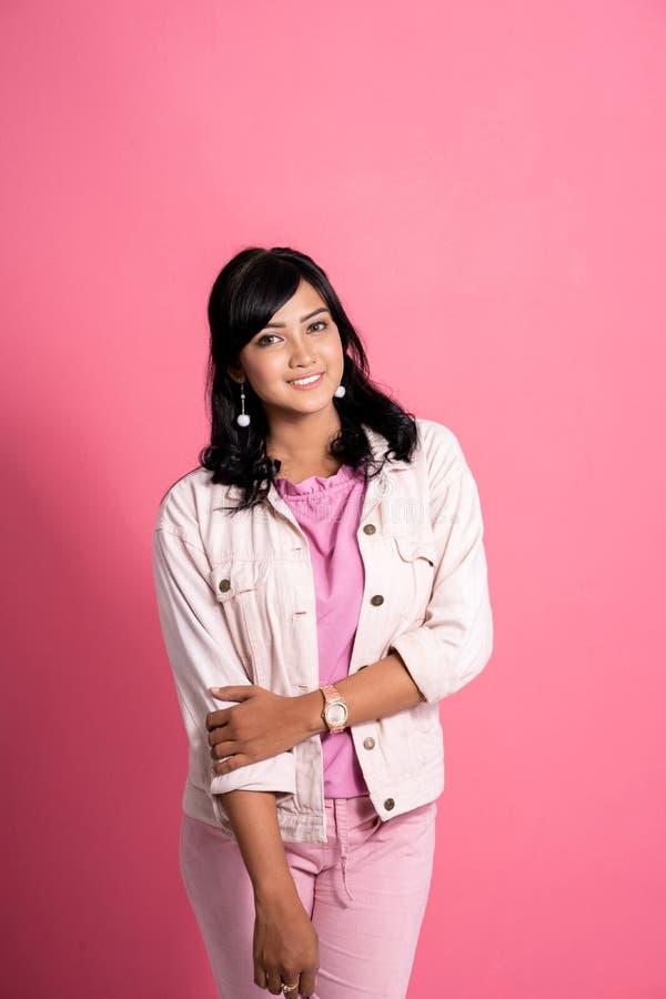 Jeune femme asiatique souriant et posant contre le rose photo libre de droits