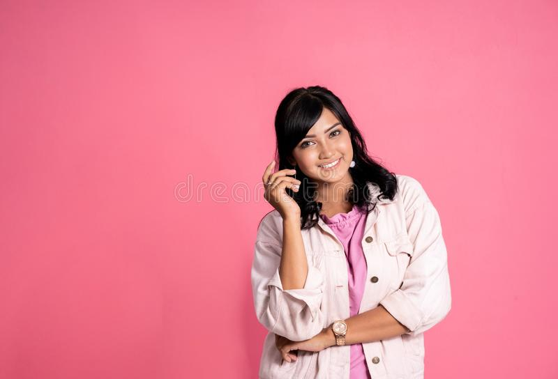 Jeune femme asiatique souriant vers la caméra au-dessus du fond rose images libres de droits
