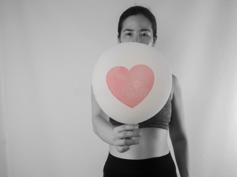 Jeune femme asiatique tenant le ballon blanc avec des sig rouges de forme de coeur images stock