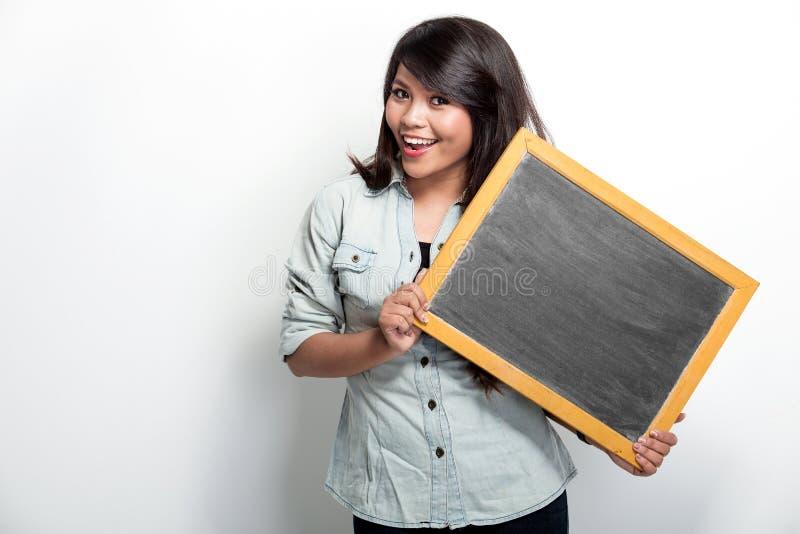 Jeune femme asiatique tenant le conseil noir vide photos stock