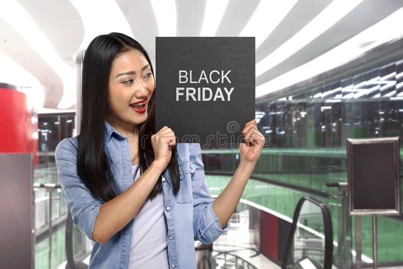 Jeune femme asiatique tenant le panneau de signe avec le texte de Black Friday images libres de droits