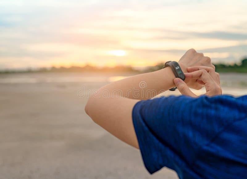 Jeune femme asiatique touchant la bande futée après fonctionnement pendant le matin Ordinateur portable Bracelet de moniteur de f image stock