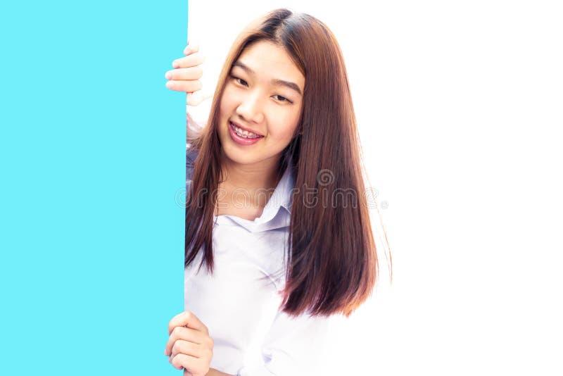 Jeune femme assez asiatique derrière une plaquette bleue sur un blanc photographie stock libre de droits
