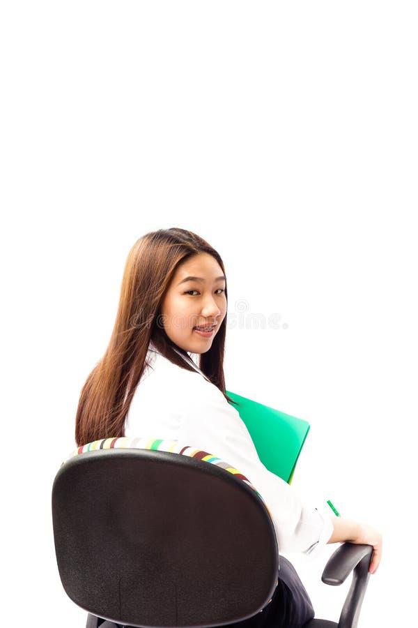 Jeune femme assez asiatique s'asseyant sur la chaise de bureau photographie stock