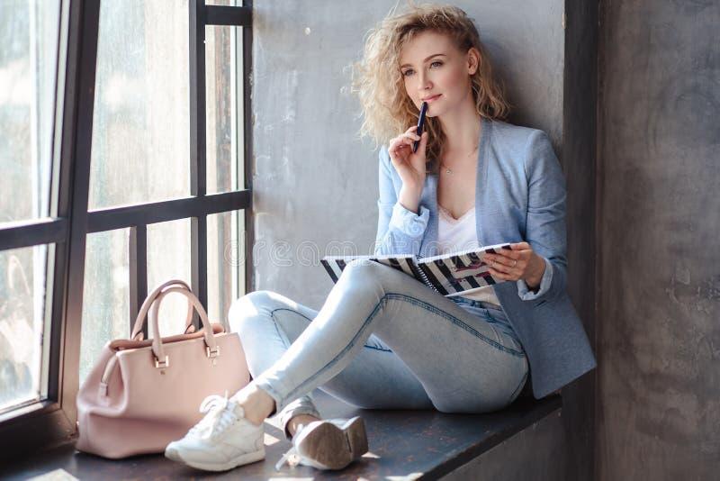 Jeune femme assez blonde d'affaires s'asseyant près de la fenêtre avec le carnet de planificateur images libres de droits
