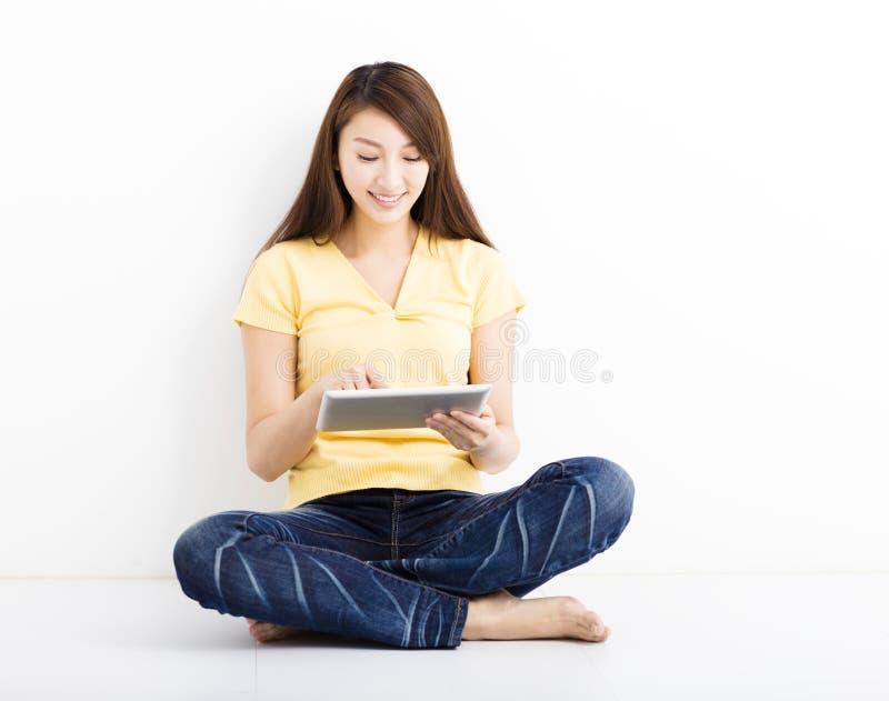 Jeune femme assise de sourire avec le PC de comprimé photo stock
