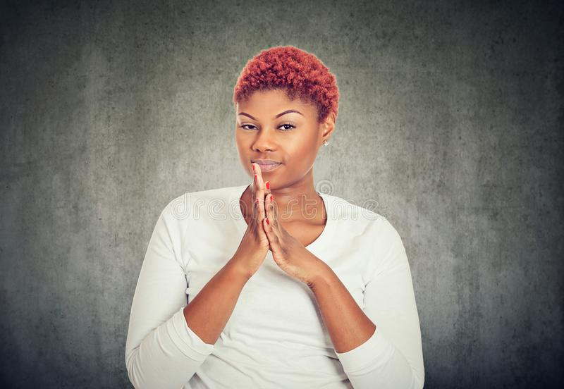 Jeune femme astucieuse tenant des mains ensemble photographie stock libre de droits