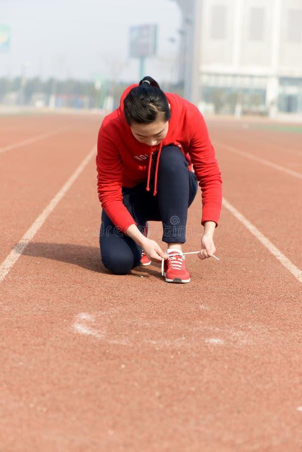 Jeune femme attachant la chaussure de sports images stock