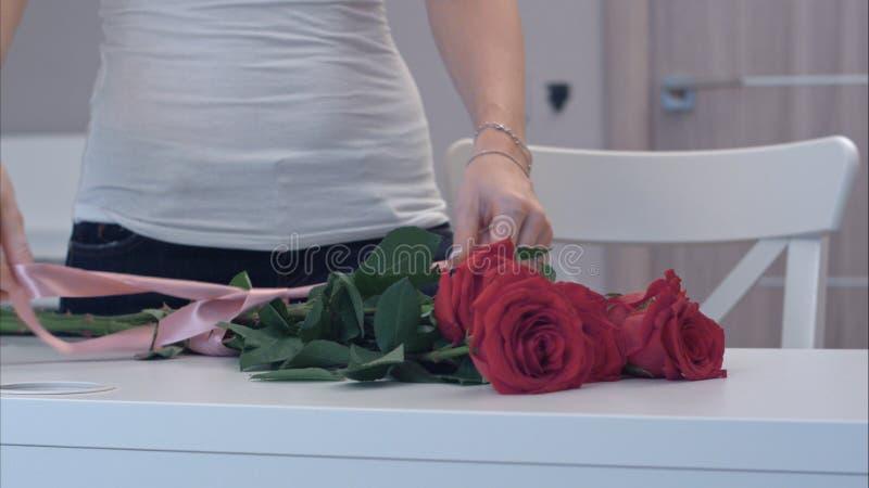 Jeune femme attachant un arc de ruban sur le bouquet de rose de rouge images libres de droits