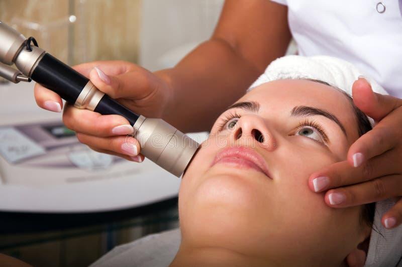 Jeune femme atteignant le nettoyage de peau le salon de beauté image stock