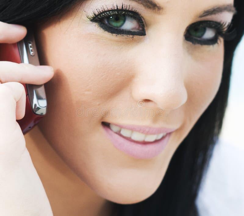 Jeune femme attirant à l'aide du téléphone portable photos stock
