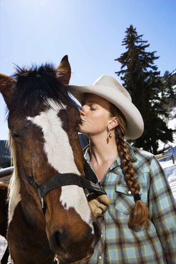 Jeune femme attirant embrassant le cheval photographie stock