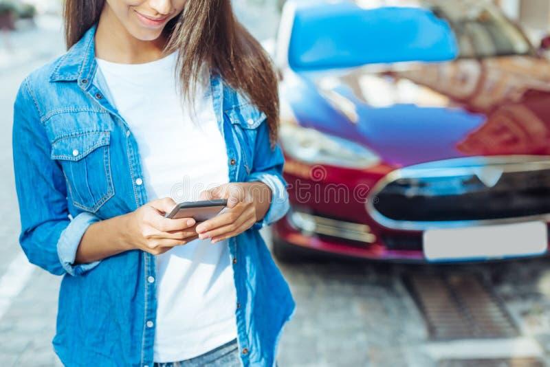Jeune femme attirante à l'aide de son smartphone photographie stock