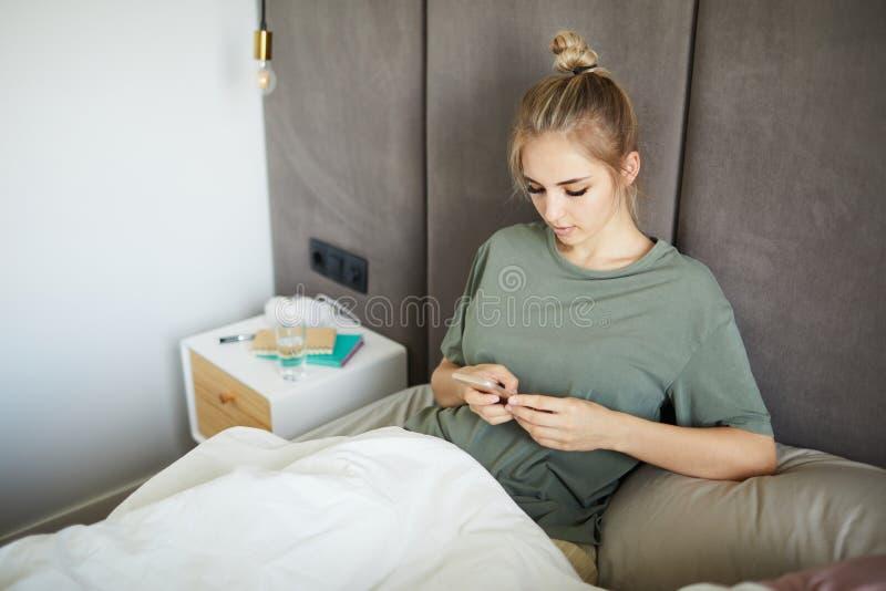 Jeune femme attirante à l'aide du smartphone dans le lit photos stock