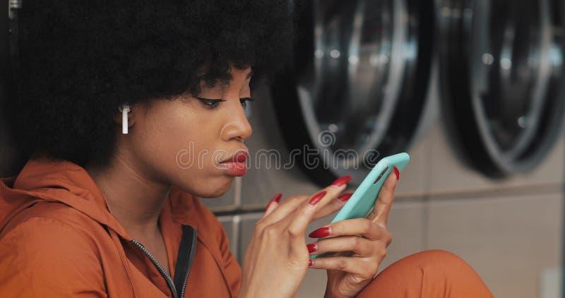 Jeune femme attirante à l'aide du smartphone à la laverie automatique Elle est port les écouteurs sans fil et chant à l'intérieur image libre de droits