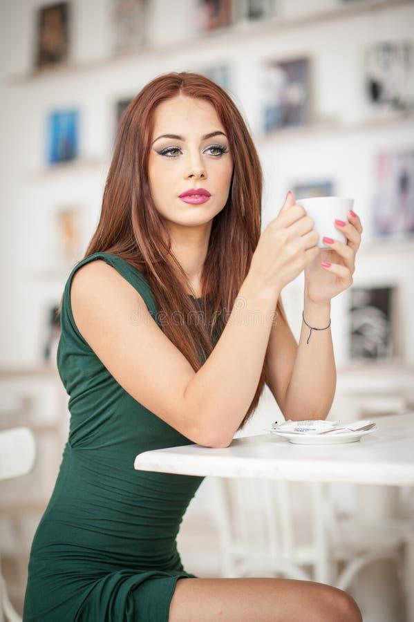 Jeune femme attirante à la mode dans la robe verte se reposant dans le restaurant Belle pose rousse dans le paysage élégant avec  image libre de droits