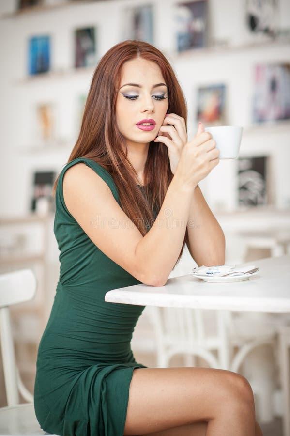 Jeune femme attirante à la mode dans la robe verte se reposant dans le restaurant Belle pose rousse dans le paysage élégant avec  image stock