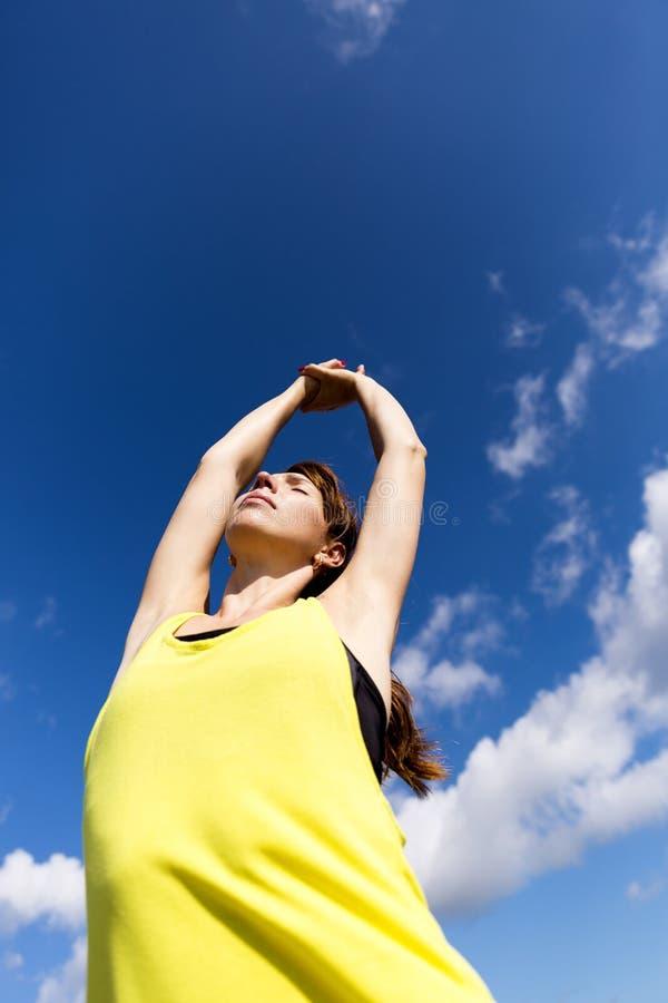 Jeune femme attirante étirant ses bras tout en se tenant contre un ciel bleu profond, s'exerçant un jour ensoleillé photographie stock