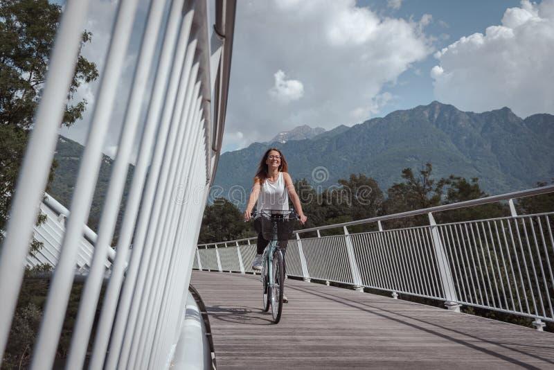 Jeune femme attirante avec la bicyclette sur un pont photographie stock