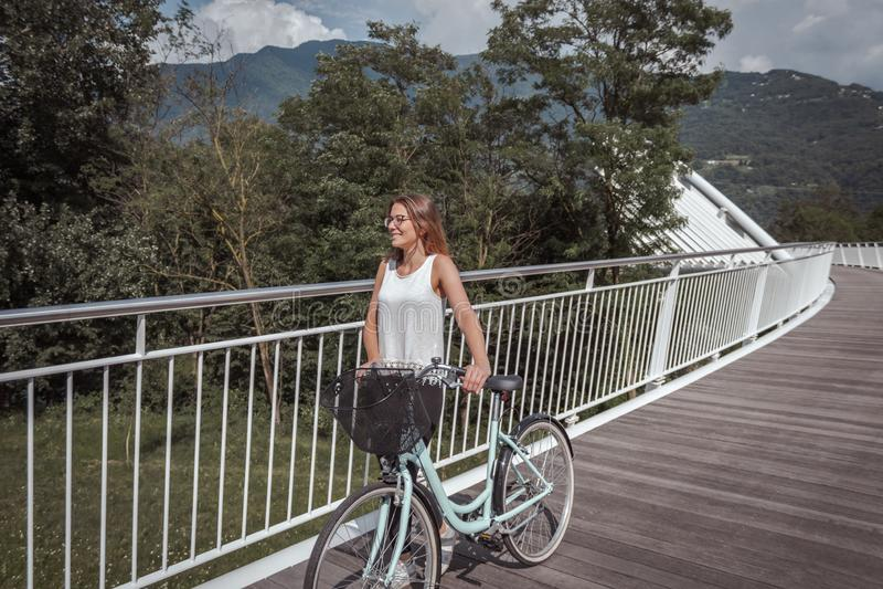 Jeune femme attirante avec la bicyclette sur un pont photos stock