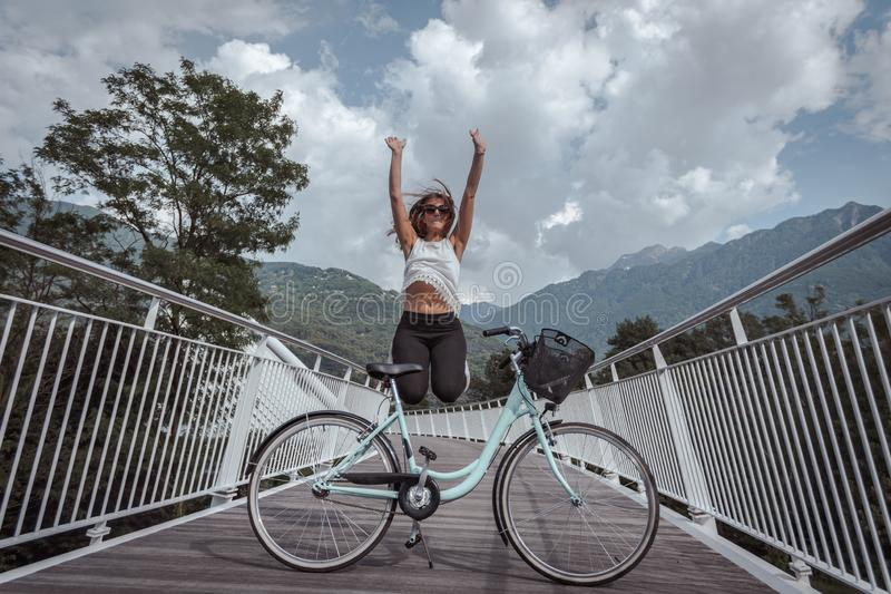 Jeune femme attirante avec la bicyclette sur un pont images stock