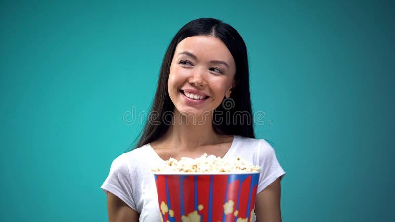 Jeune femme attirante avec la grande tasse de maïs éclaté souriant et flirtant dans le cinéma images libres de droits