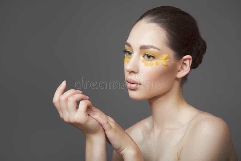 Jeune femme attirante avec la peau propre parfaite Pétales des fleurs sur son visage Concept de soin de peau Fond gris Renivellem image stock