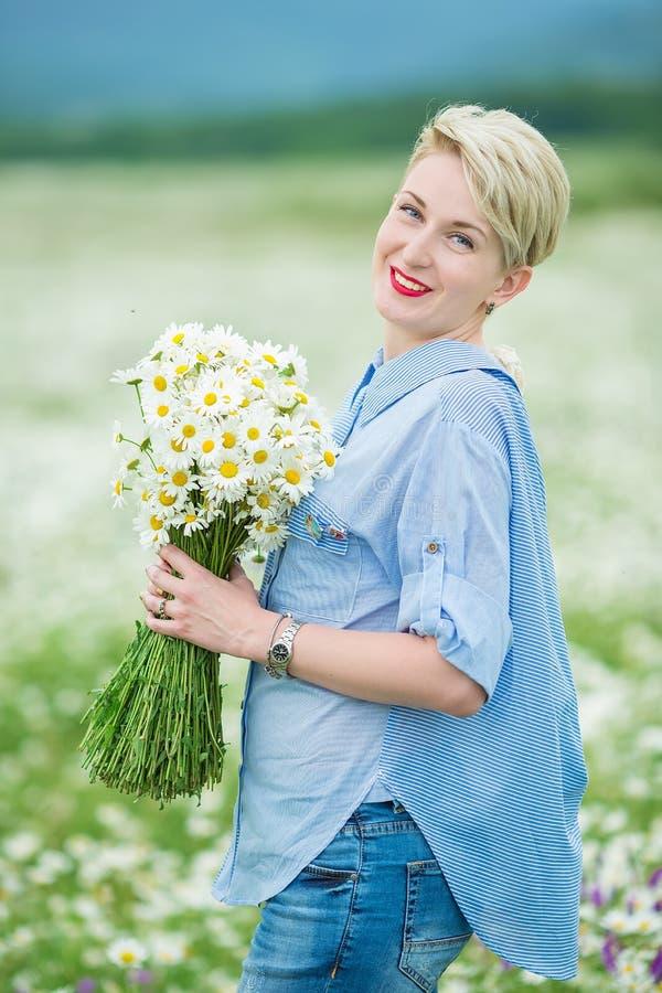 Jeune femme attirante avec le bouquet de camomille marchant par le champ de camomille Extérieur blond actif image stock