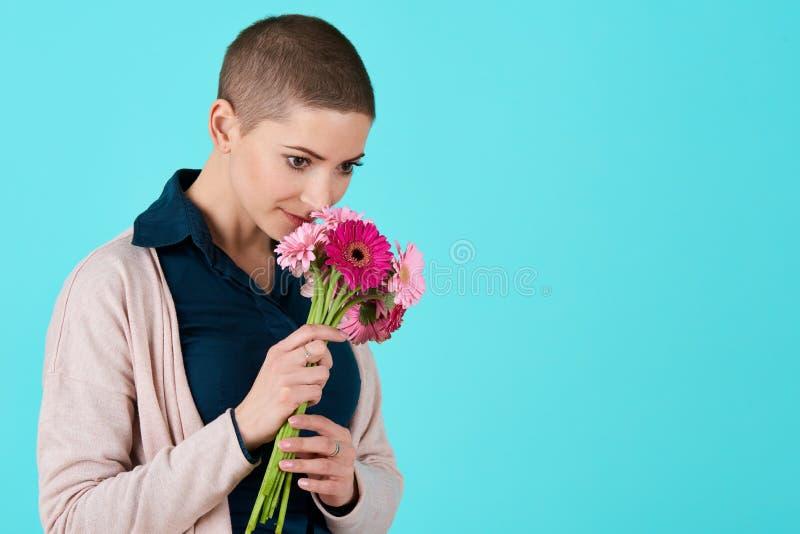 Jeune femme attirante avec le bouquet sentant de cheveux courts des marguerites roses de gerbera Joyeux anniversaire photos libres de droits