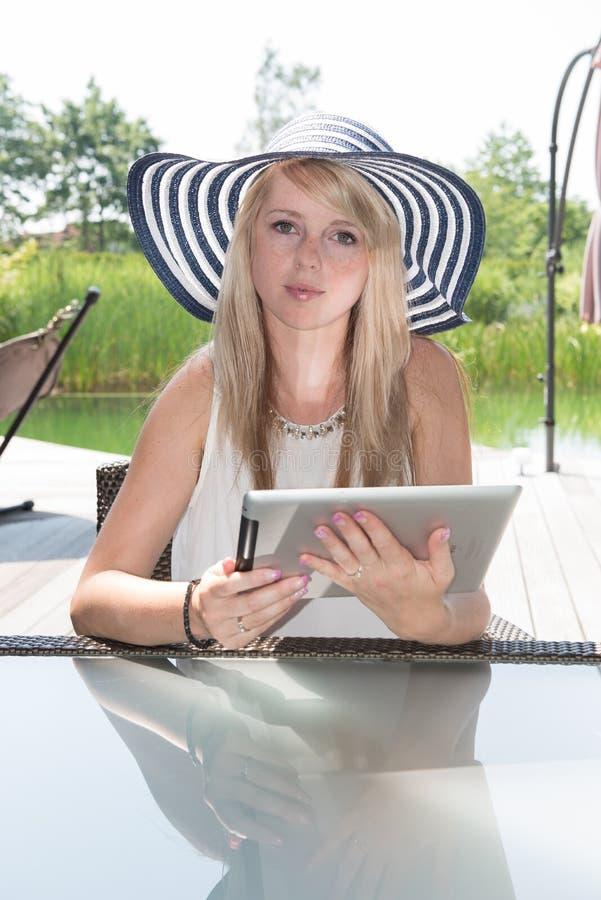 Jeune femme attirante avec le chapeau travaillant au comprimé photographie stock libre de droits
